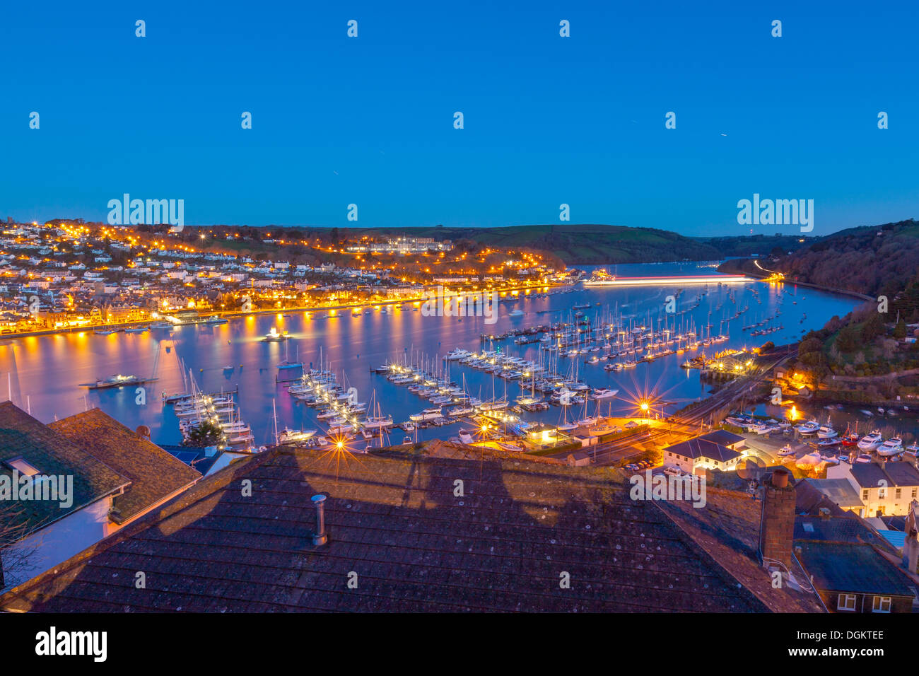 Boats moored on the river Dart with Dartmouth in the background. - Stock Image