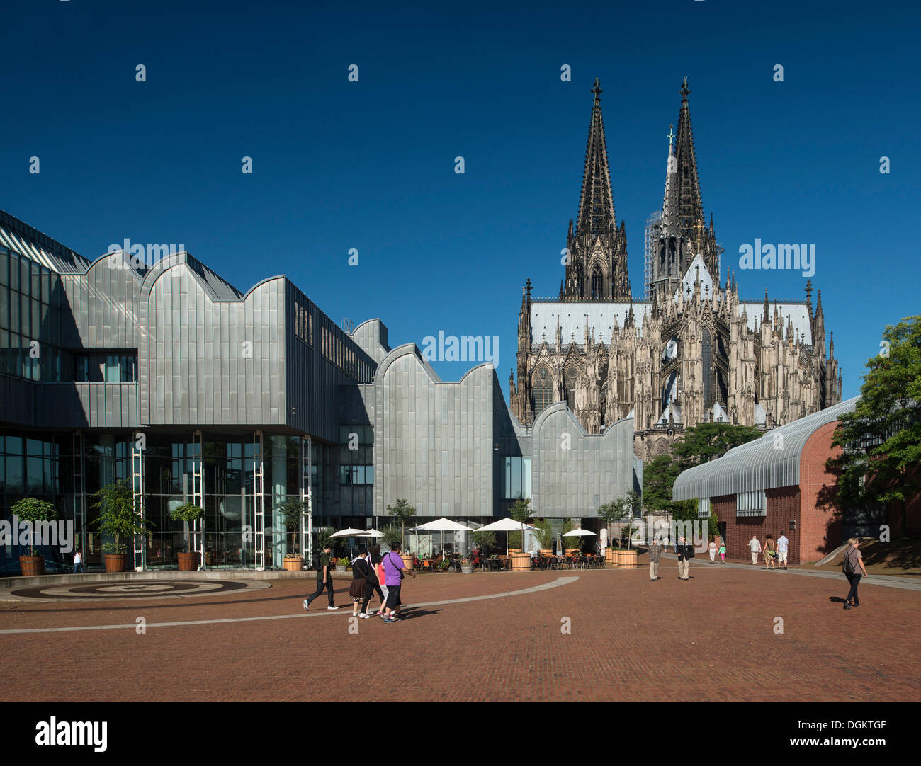 View of the Ludwig Museum and Cologne Cathedral as seen from Heinrich-Boell-Platz square, tourists walking in the foreground - Stock Image