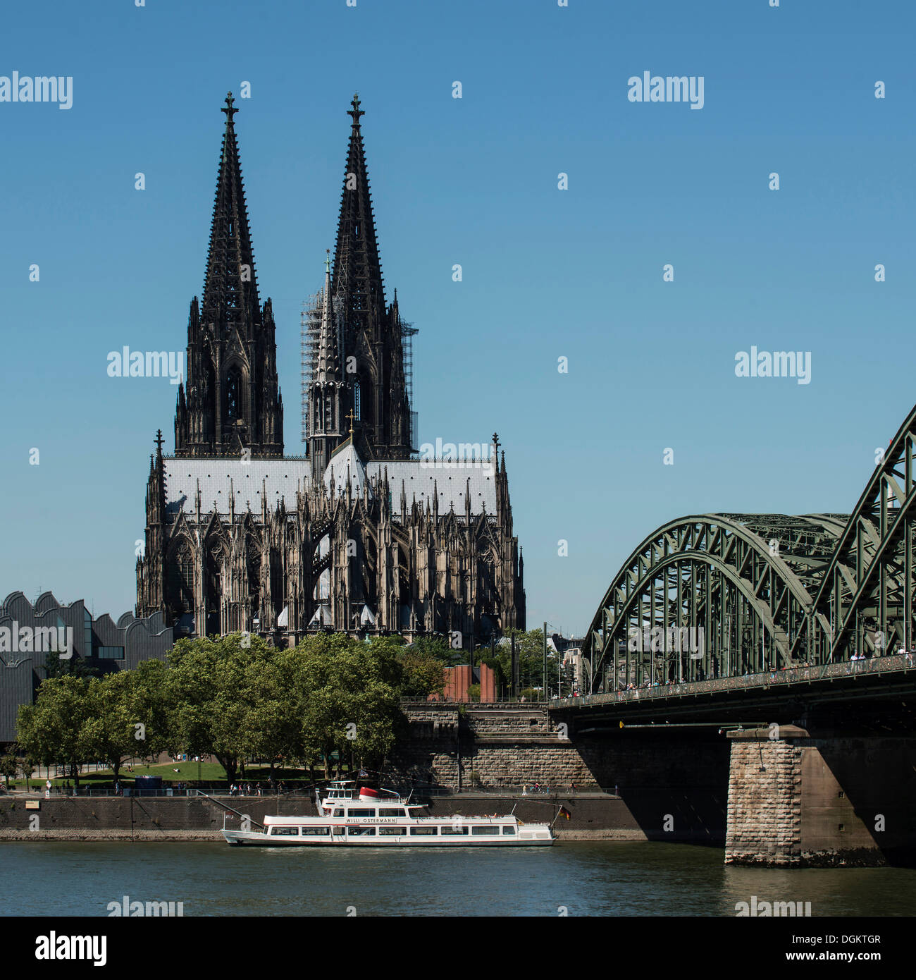 View as seen from Deutz across the Rhine river, Hohenzollernbruecke bridge, Willi Ostermann excursion boat in the foreground - Stock Image