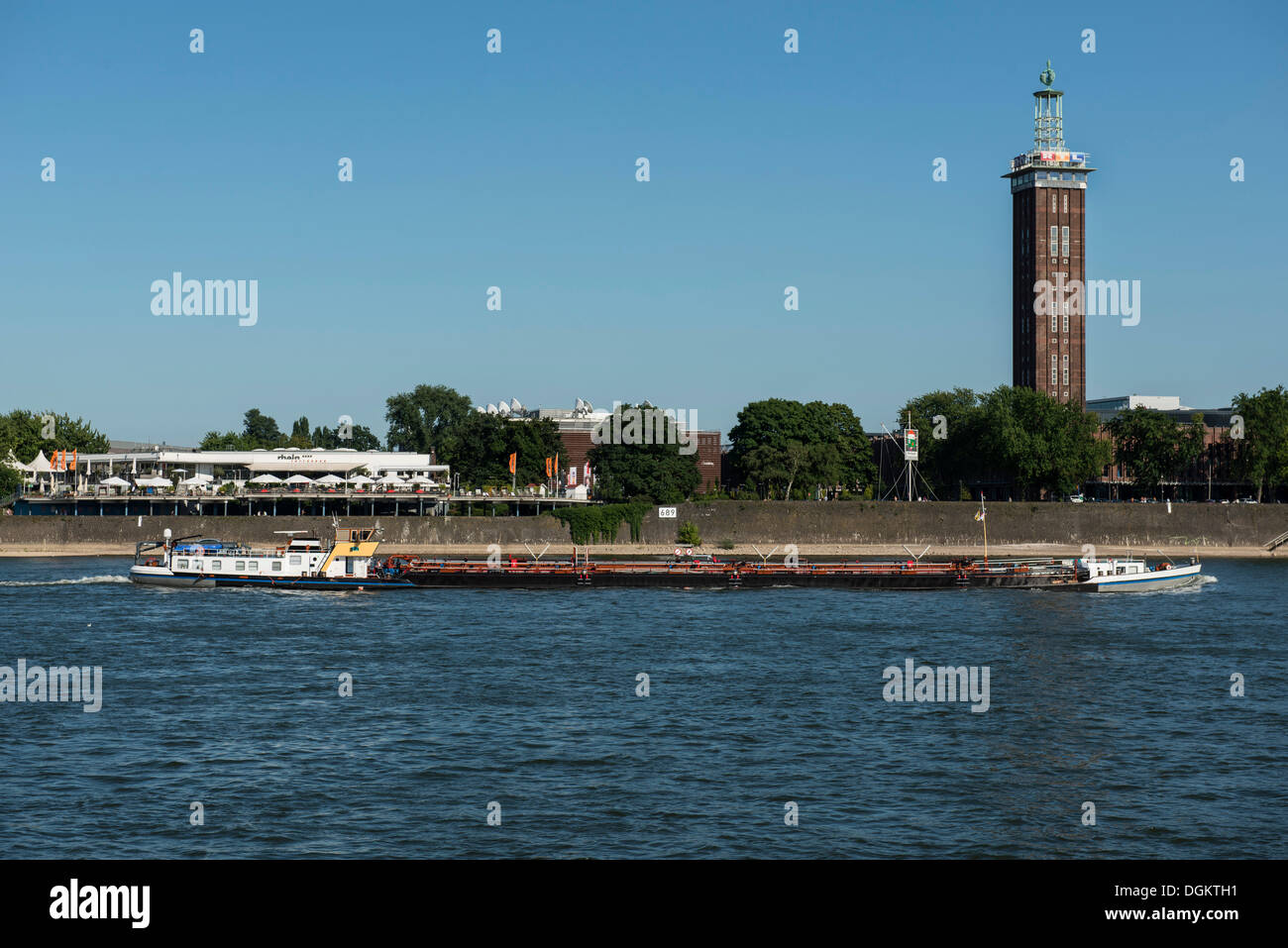 Benny, an inland vessel traveling up the Rhine river, Tanzbrunnen venue and the historic Messeturm tower at the back, Cologne - Stock Image