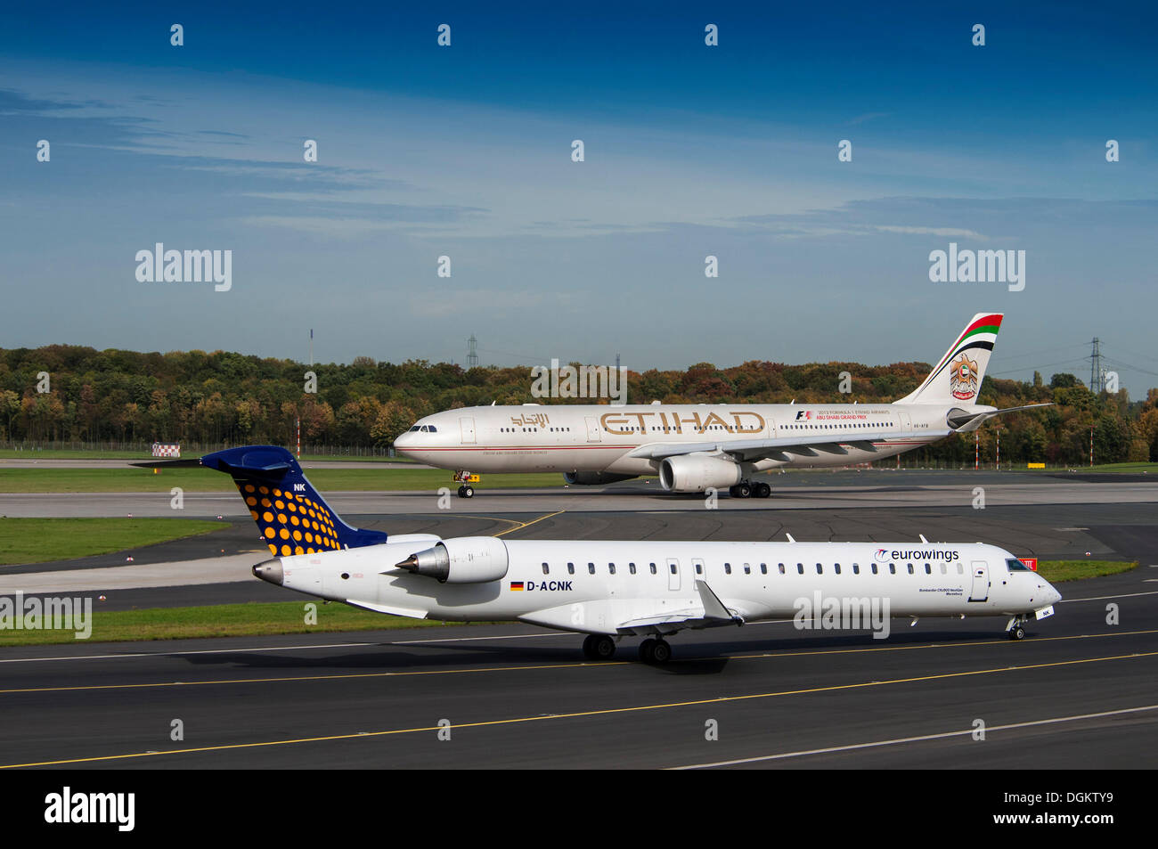 Two aircrafts on the runway, Bombardier CRJ900 of EuroWings, behind Airbus A330-343x of the Ethihad Airways, Düsseldorf - Stock Image