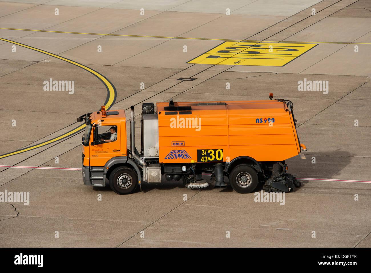 Sweeper in action on the runway, Duesseldorf International Airport, North Rhine-Westphalia - Stock Image