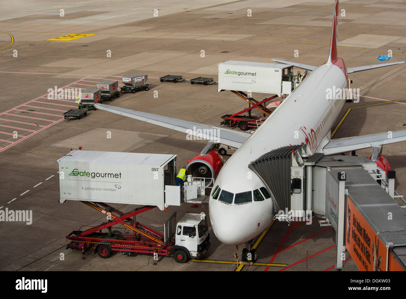 Aircraft is being prepared for the flight, elevating platform truck delivering goods for the galley, baggage car - Stock Image