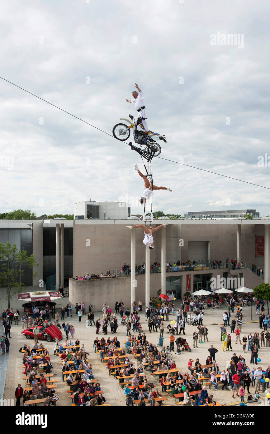 Museum Mile Festival, high-wire artist Falko Traber riding a motorbike on the tightrope, audience below, Bonn - Stock Image