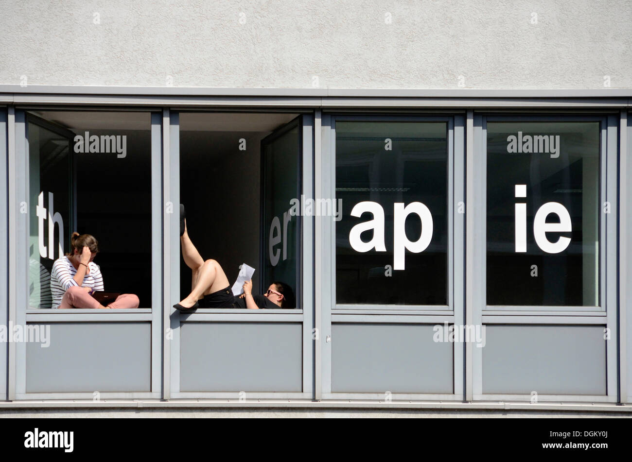 Students of a school for physical therapy taking a break and reading at windows with the word 'therapie', Hamburg, Hamburg - Stock Image