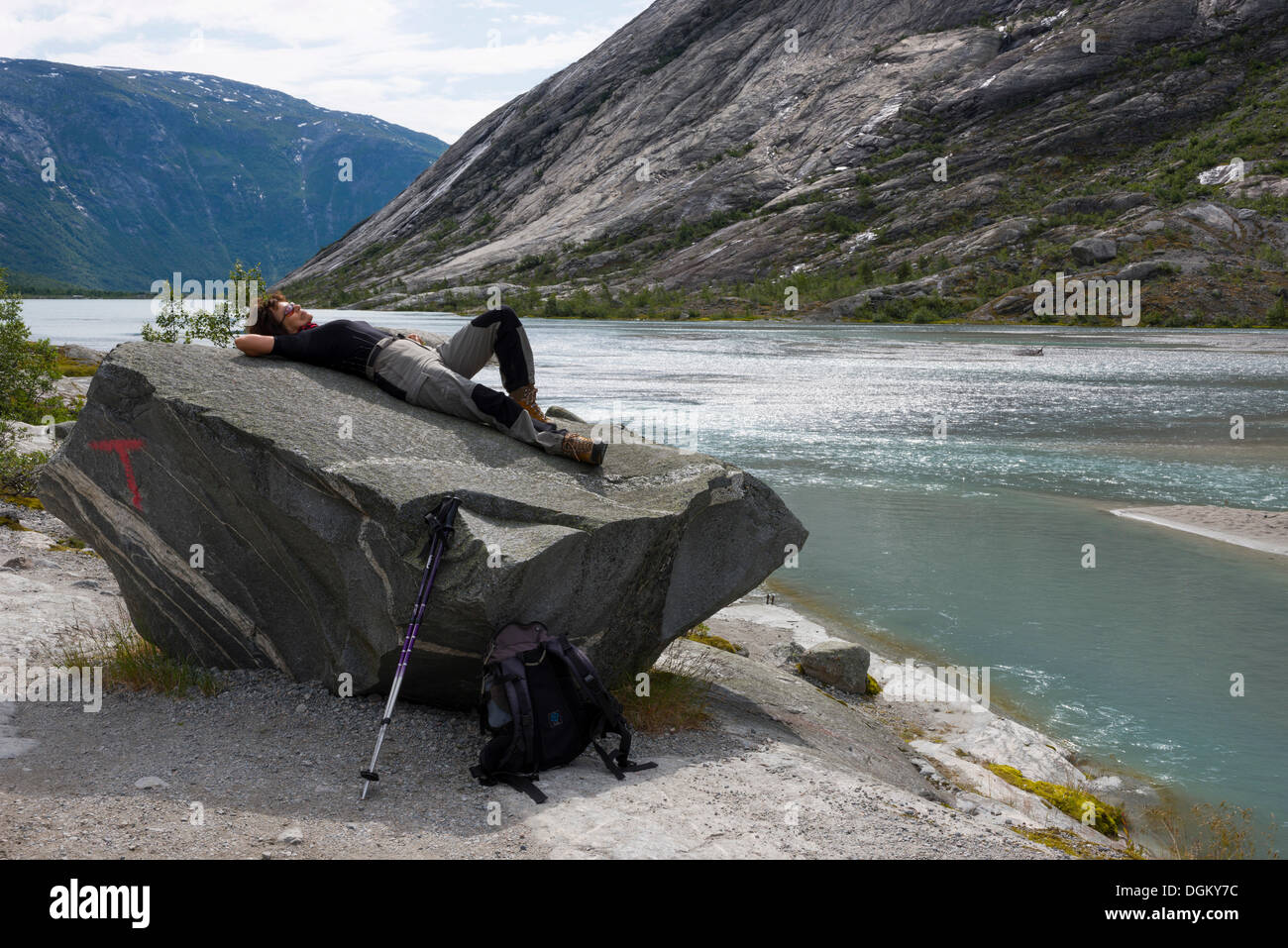 Woman wearing hiking clothing lying on a prominent boulder at the glacial lake of Nigardsbrevatnet, Jostedal - Stock Image