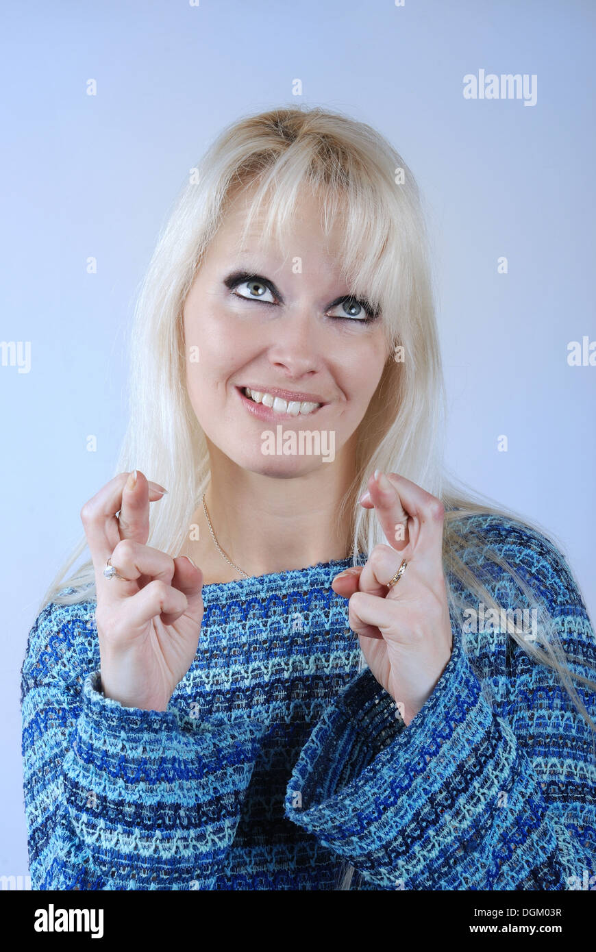 Young blond woman fingers crossed - Stock Image