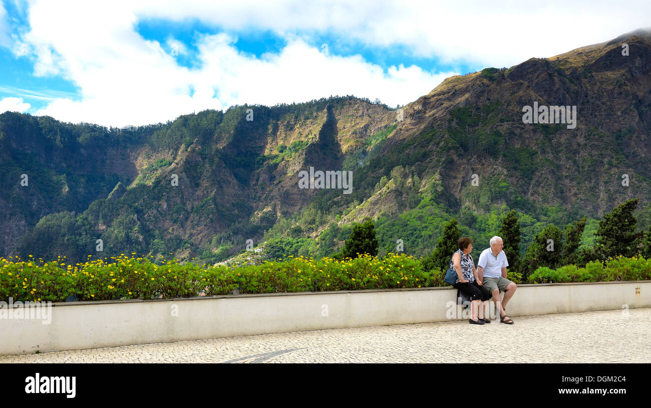 Curral das Freiras Madeira. Tourists sitting on a wall with mountain scenery behind also known as Nuns valley - Stock Image