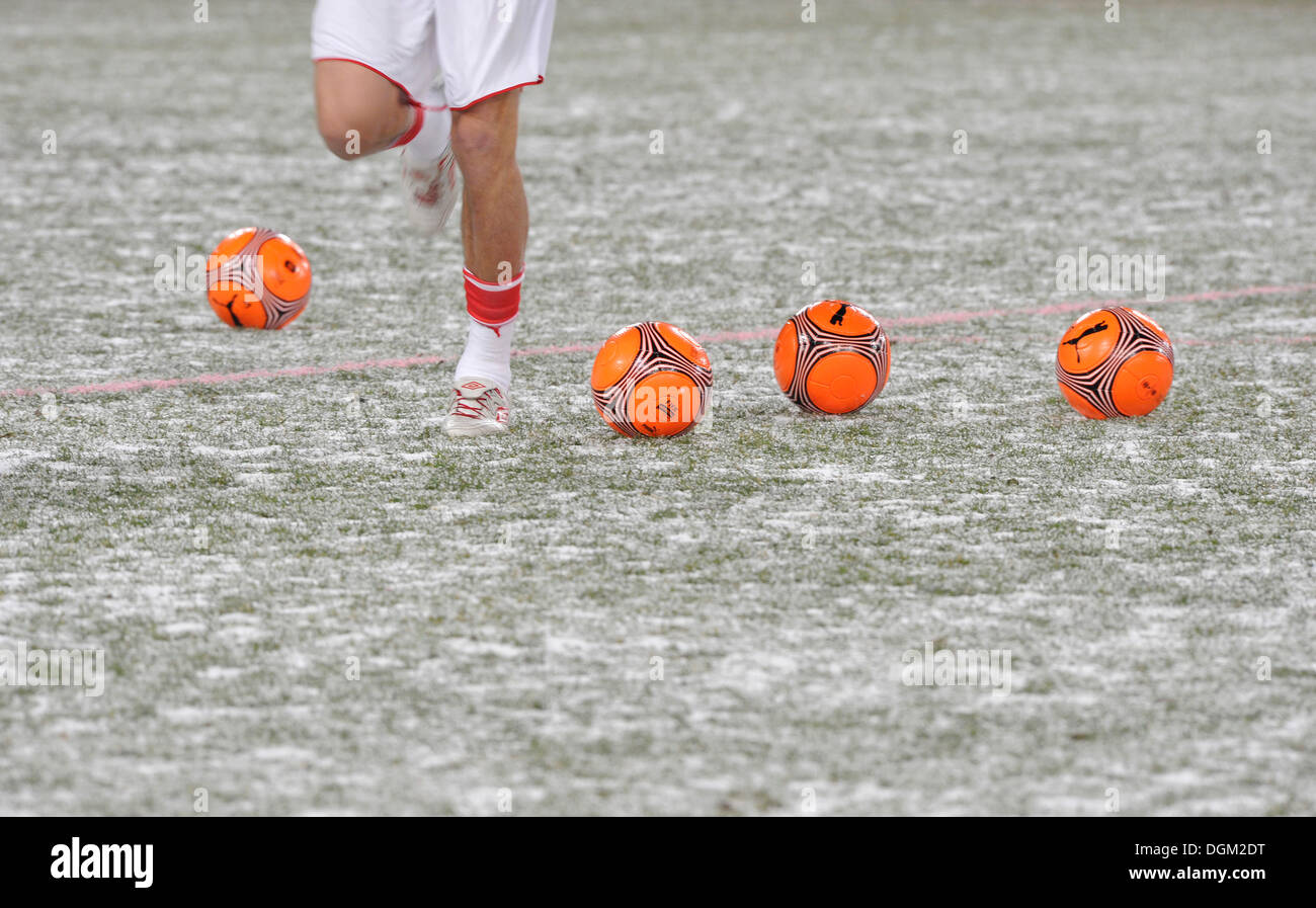 Warm-up training with orange footballs for the winter on snow-covered pitch - Stock Image