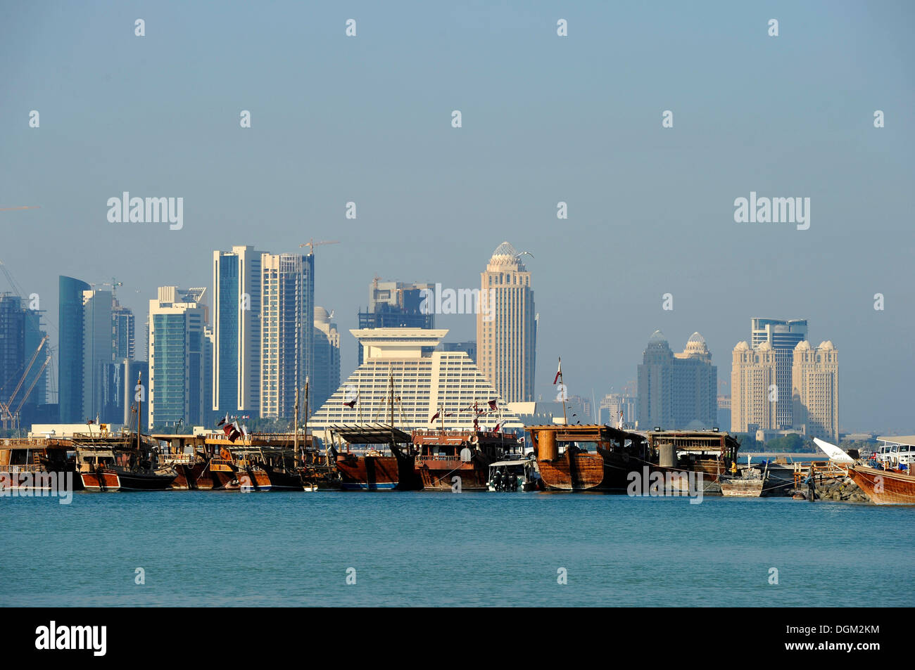 Tradition and modernity, dhow wooden cargo ships in front of the skyline of Doha, Qatar, Persian Gulf, Middle East, Asia - Stock Image