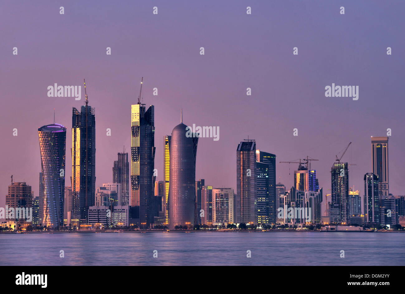 Skyline of Doha, Tornado Tower, Navigation Tower, Peace Towers, Al-Thani Tower, at dusk, Qatar, Persian Gulf, Middle East, Asia - Stock Image