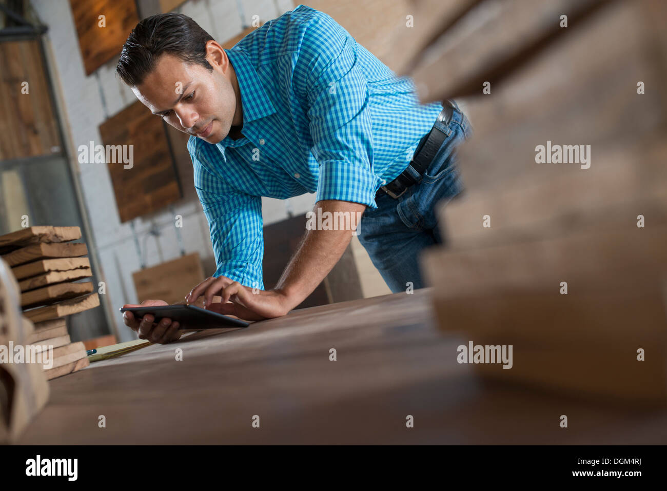 A young man in a workshop Using a digital tablet in his work. - Stock Image
