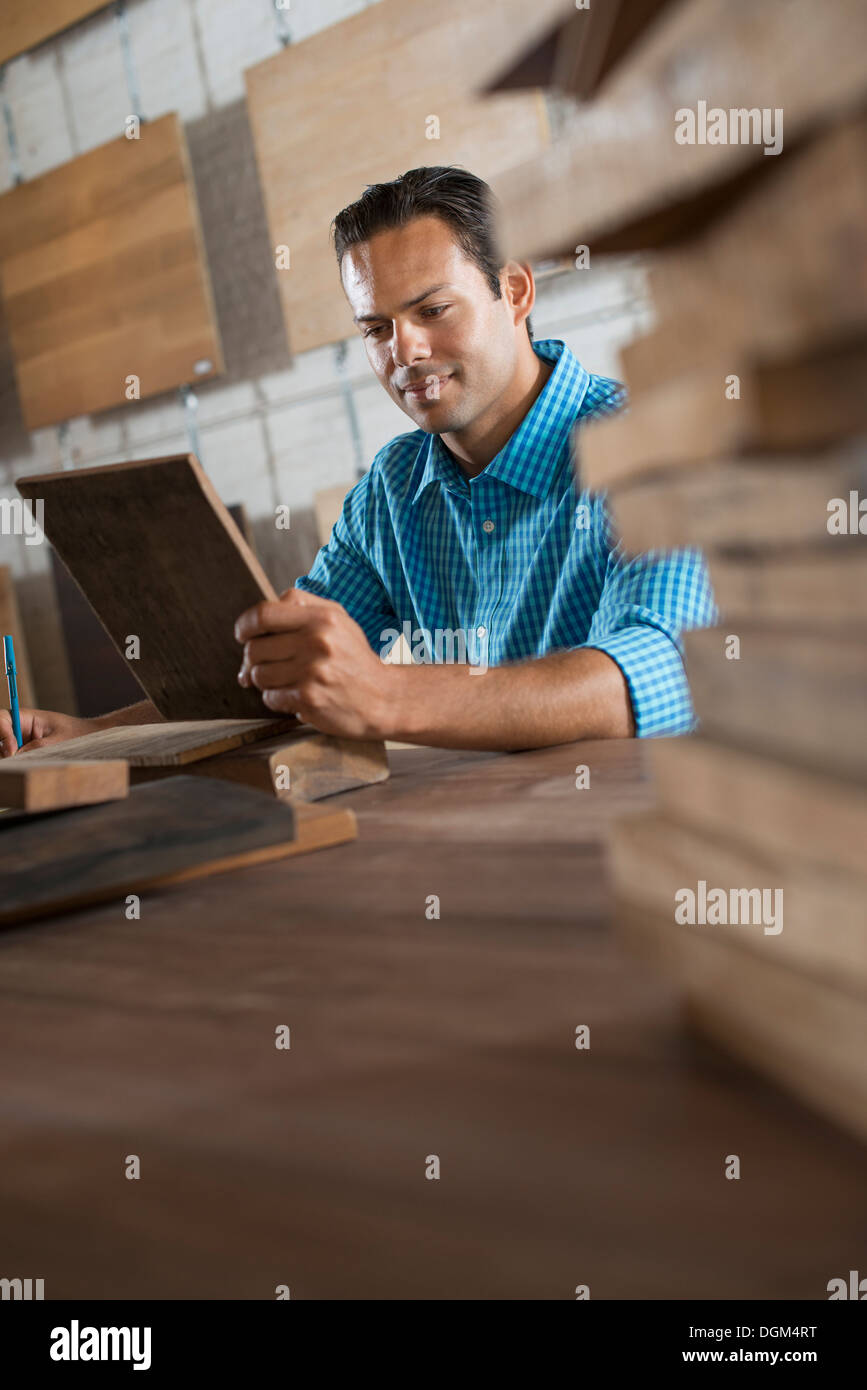 A young man in a workshop. Examing a wood sample and taking notes on paper. - Stock Image