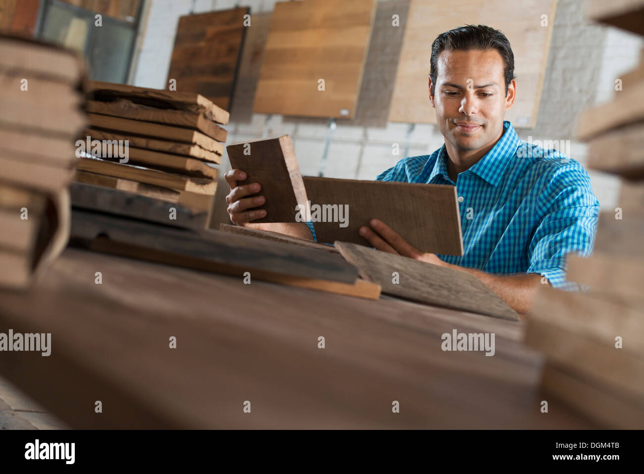 A young man in a workshop. Examining a reclaimed wood sample. - Stock Image