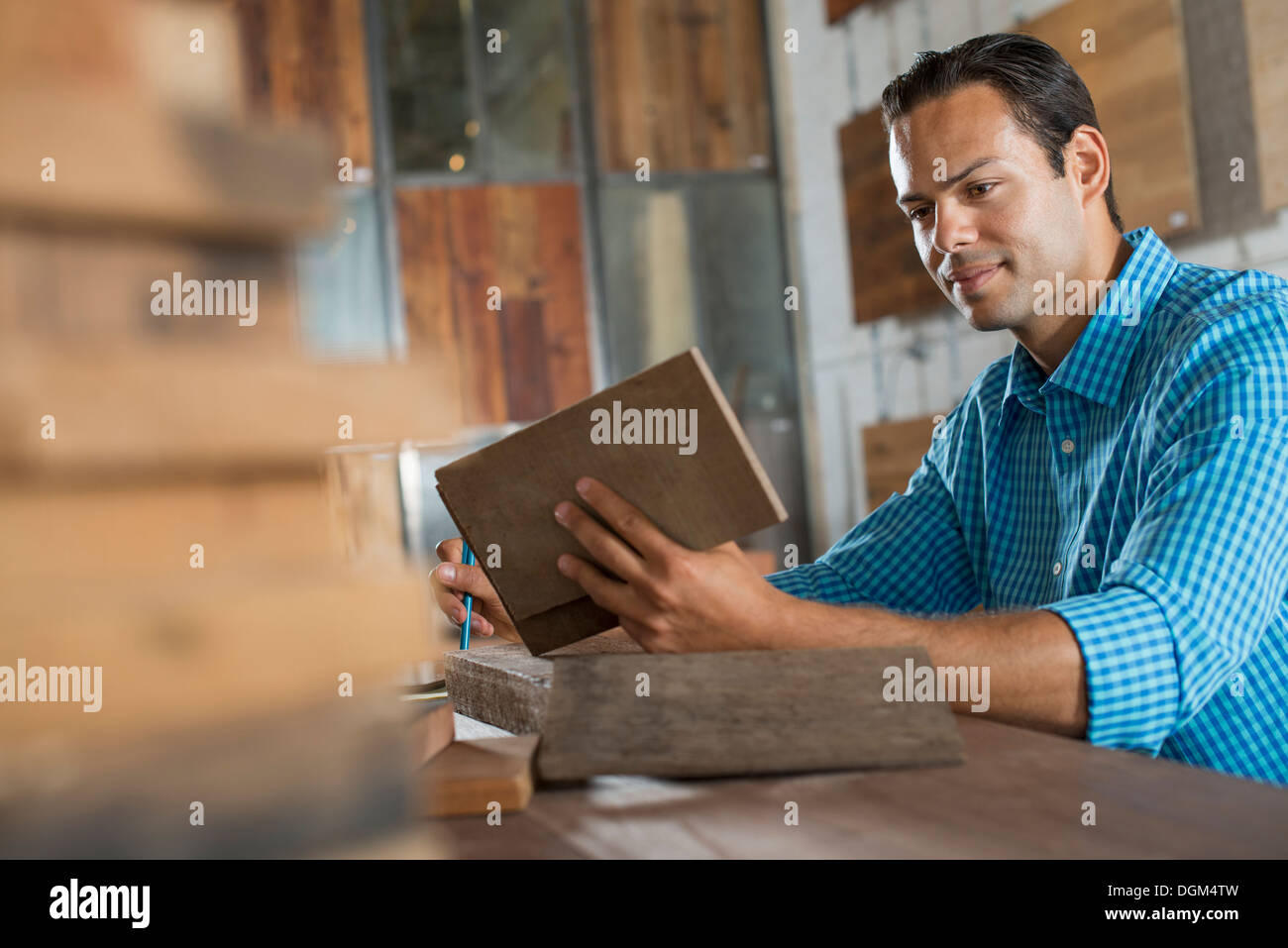 A young man in a workshop examining a recycled wood sample. - Stock Image
