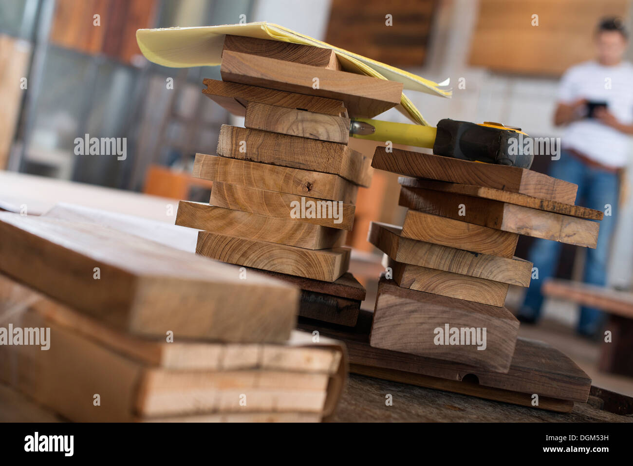 A young man in a workshop. Using a digital tablet to keep records and photograph objects. - Stock Image