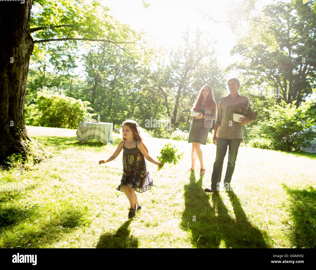 On the farm. Two adults carrying cartons of fresh vegetables and plants. A girl carrying bunches of fresh herbs. - Stock Image