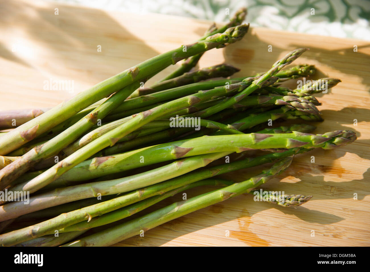 On the farm. A chopping board and sharp kitchen knife. A bunch of freshly picked organic asparagus. - Stock Image