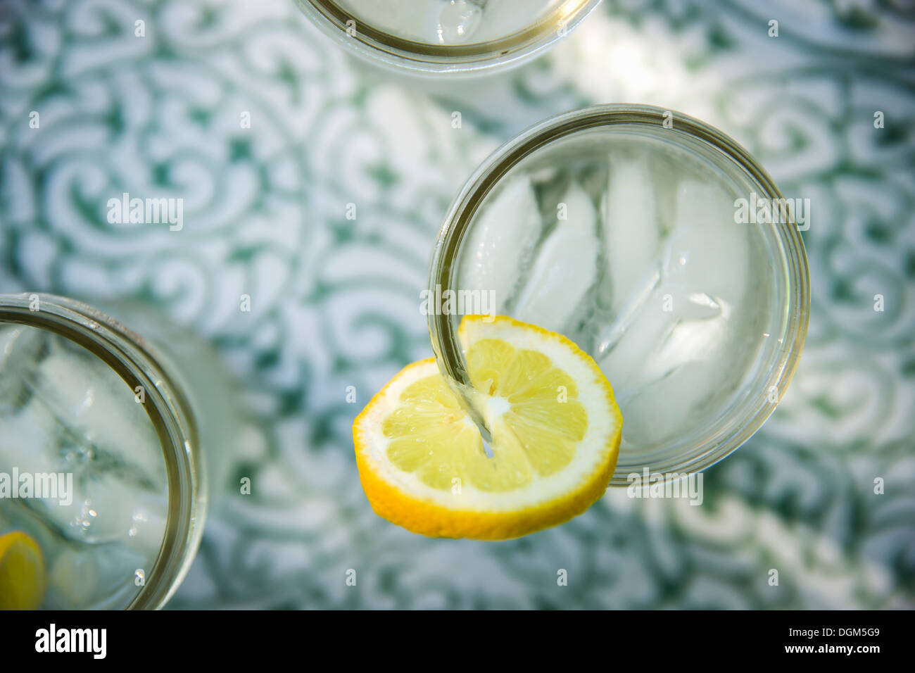 Making lemonade Overhead shot of lemonade glasses fresh slice of lemon in edge of glass Organic lemonade drinks Stock Photo