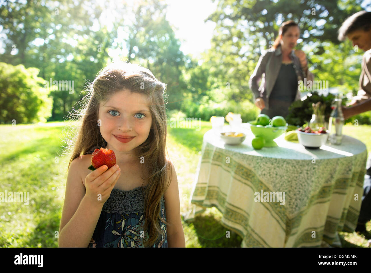 A young girl holding a large fresh organically produced strawberry fruit. Two adults beside a round table. - Stock Image