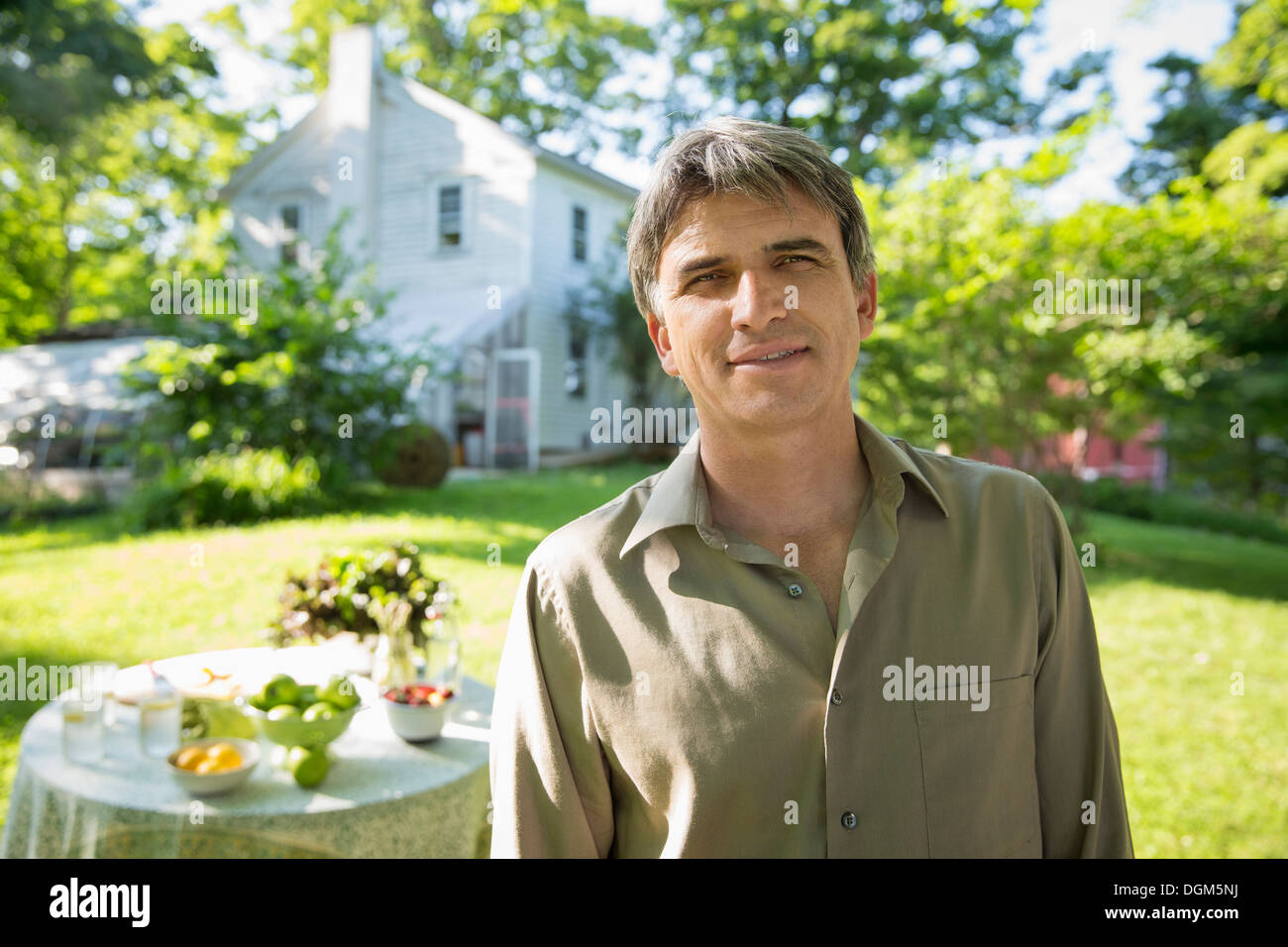 On the farm. A man in a farmhouse garden, beside a round table with fresh lemonade drinks. - Stock Image