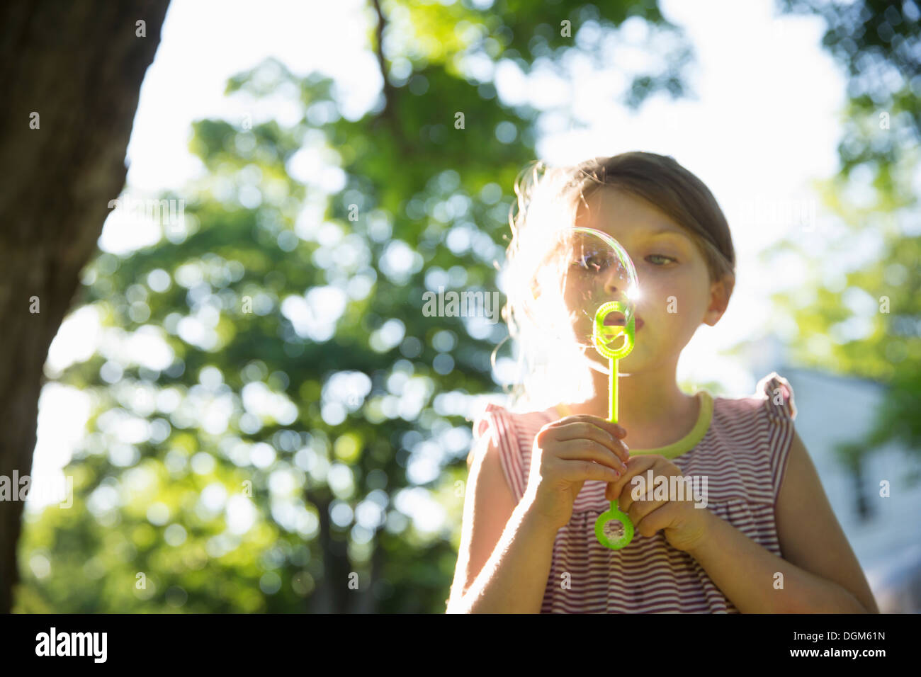 Outdoors in summer. A young girl blowing bubbles in the air under the branches of a large tree. Stock Photo