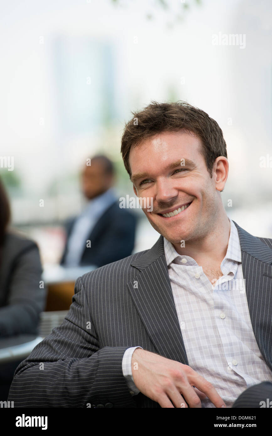 Summer. A young man with open collar and jacket sitting on a bench. - Stock Image