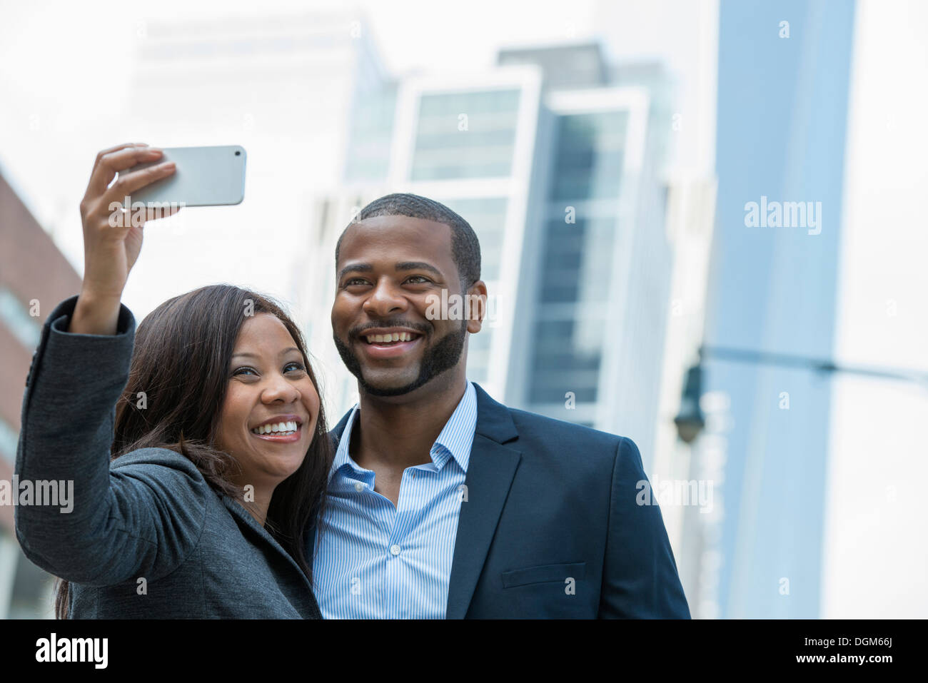 Summer. A couple taking a selfy, a woman holding out a smart phone and taking their picture. - Stock Image