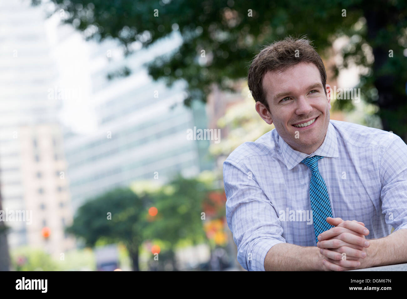 Summer. A man in a white shirt and blue tie with his hands clasped, leaning on a railing. - Stock Image