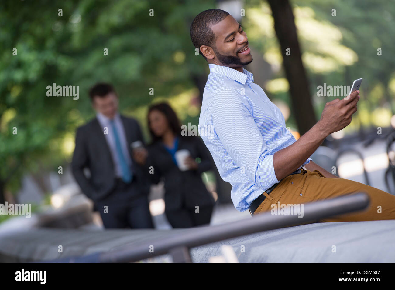 Summer in the city. A young man in a grey suit and blue tie walking with a woman in a suit. A man seated on a bench. - Stock Image