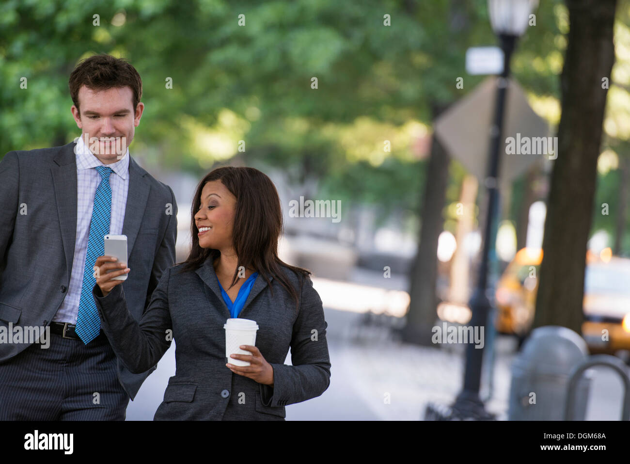Summer. A young man in a grey suit and blue tie walking with a woman in a suit. White man, black african american woman - Stock Image