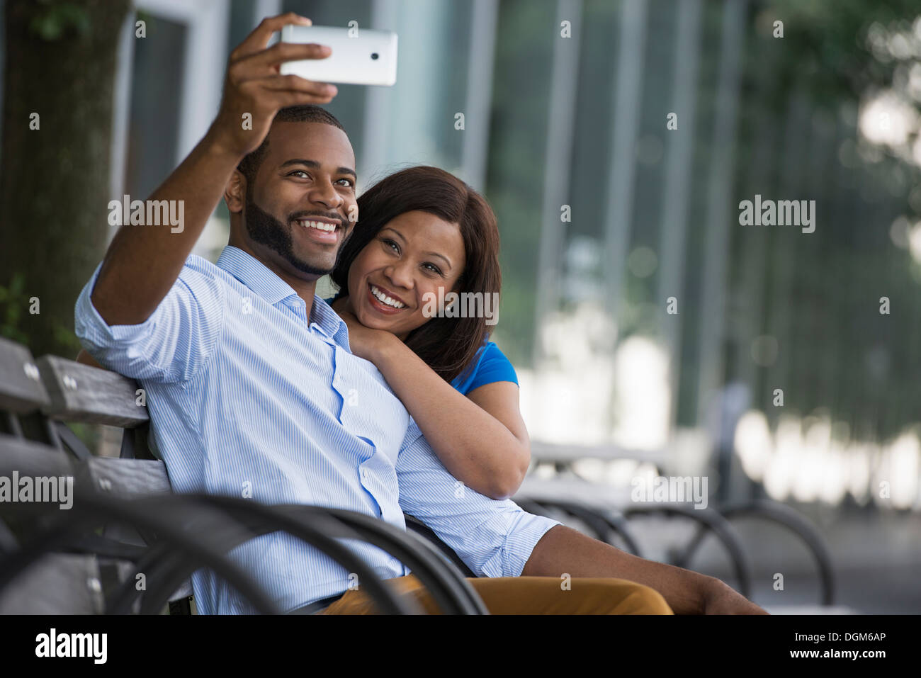 Summer. A couple sitting on a bench, taking a selfy photograph. - Stock Image