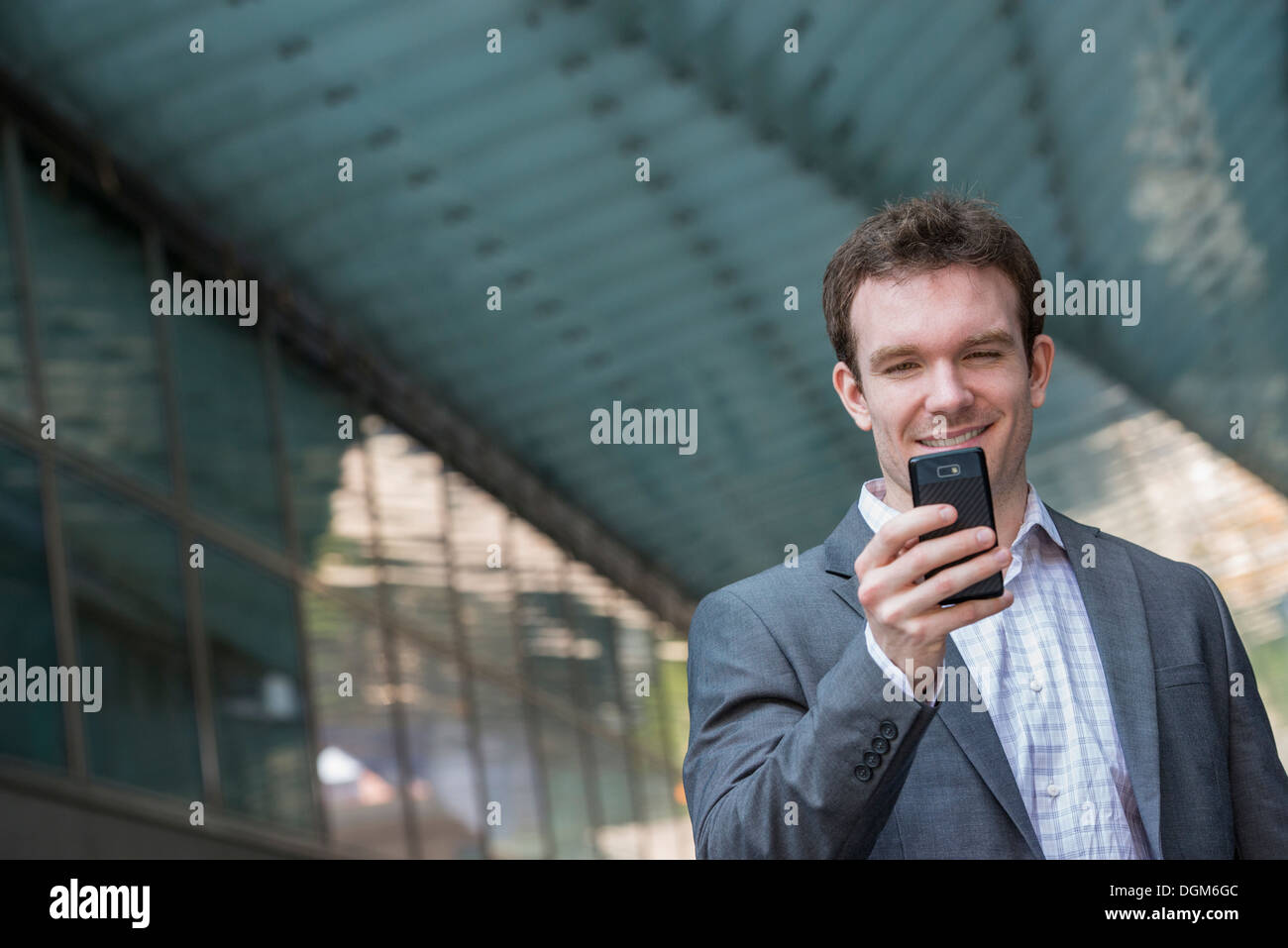 Summer. A young man in a grey suit and blue tie. Using a smart phone. - Stock Image