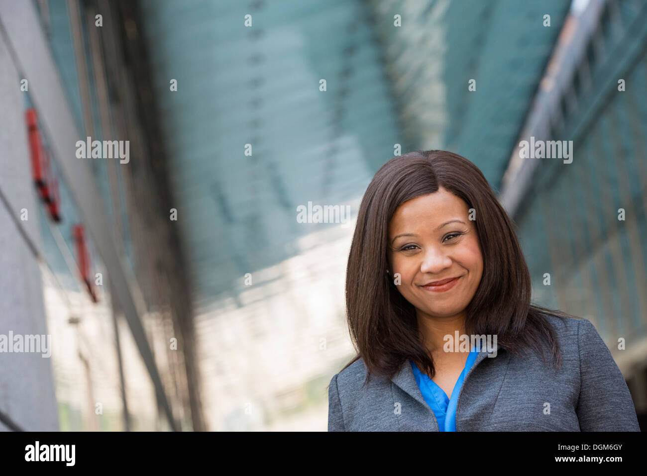 Summer. A woman in a grey suit with a bright blue shirt. - Stock Image