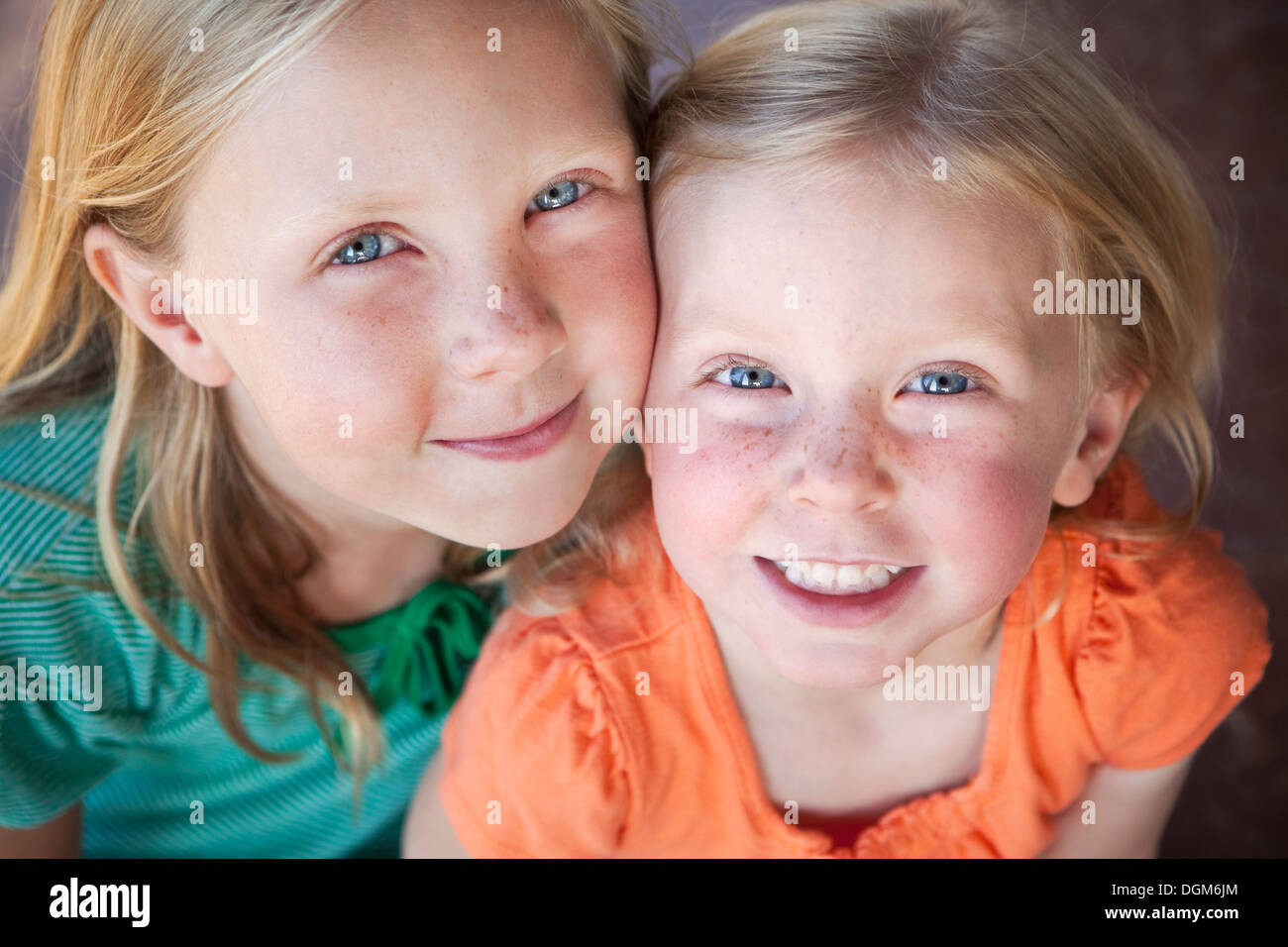 A Portrait Of Two Sisters Smiling. Two Young Girls, With