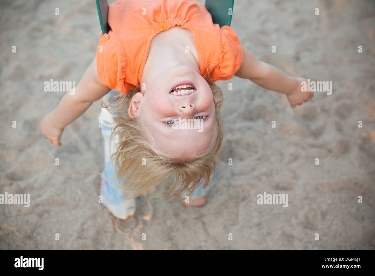 A child playing outdoors. A girl hanging upside down on a swing. - Stock Image