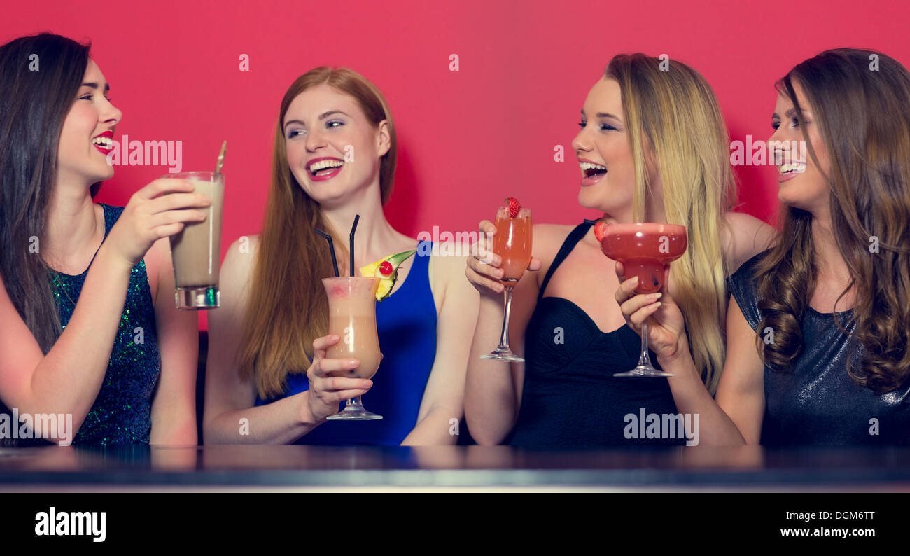 Attractive friends clubbing holding cocktails - Stock Image