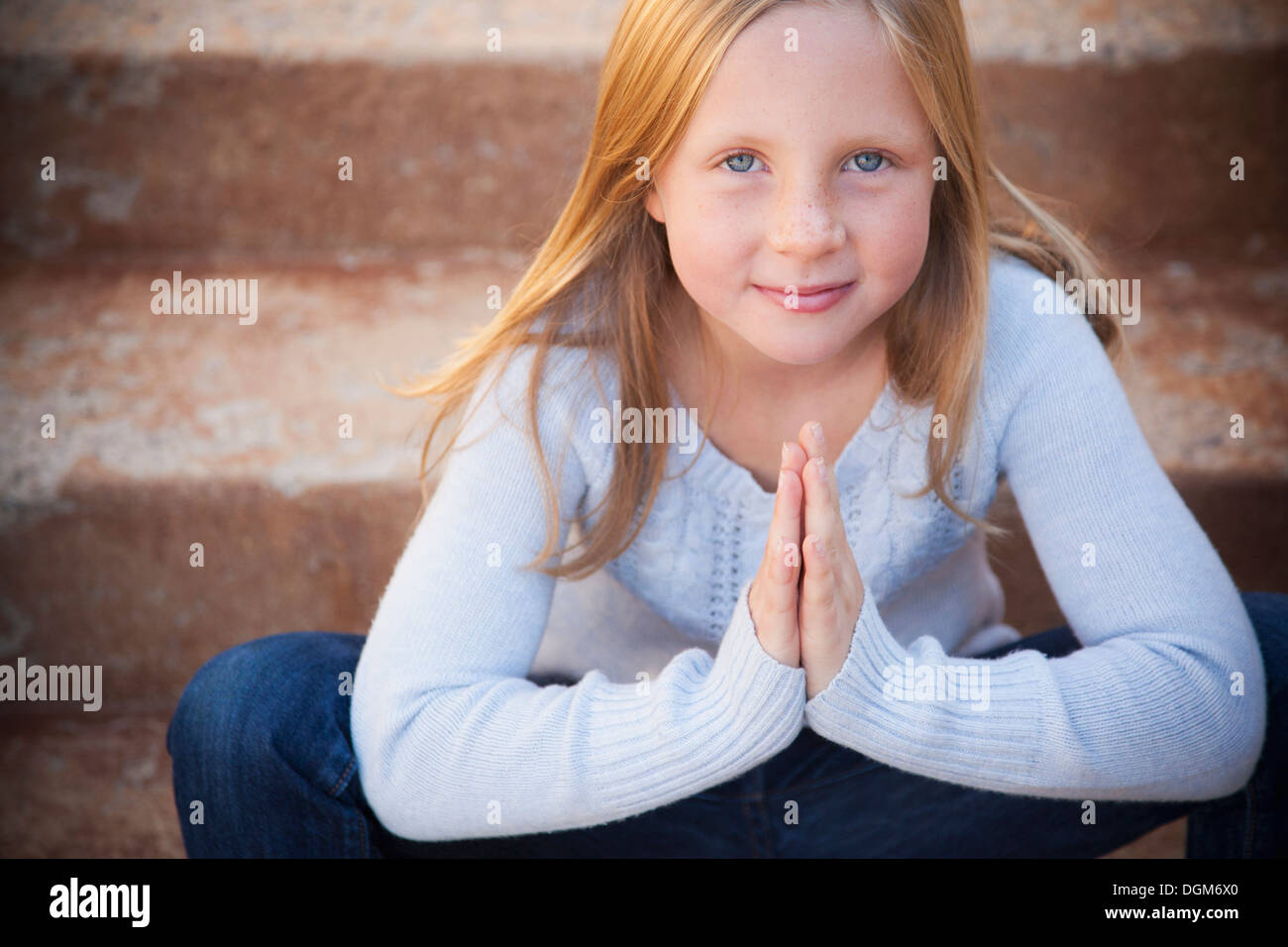 A young girl seated on the steps of a garden, with her hands pressed, palms together. - Stock Image