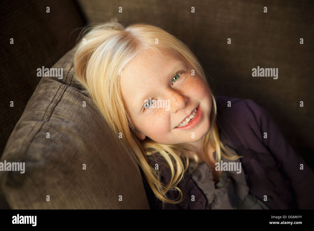A girl sitting on a couch, smiling at the camera. - Stock Image