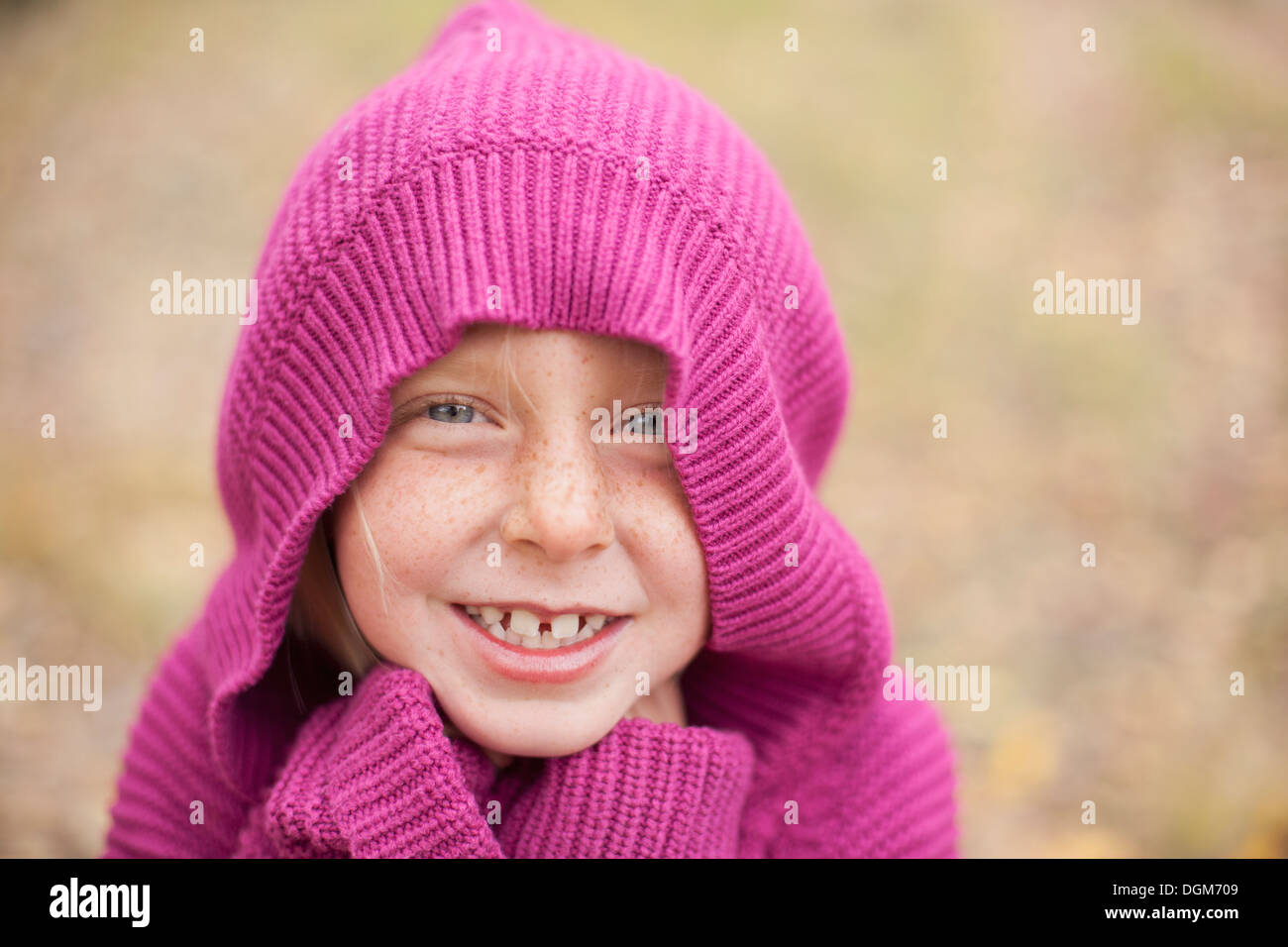 A girl in a magenta hooded sweater, with the hood covering her head Stock Photo