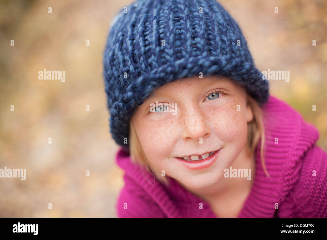 A girl in a knitted hat, and magenta jumper with a folded collar. Stock Photo