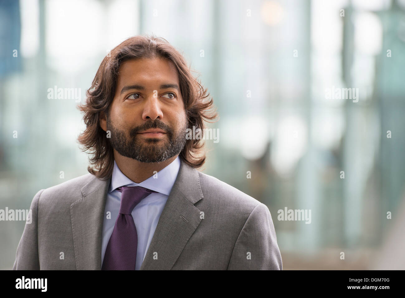 Business people out and about in the city. A Latino man in a suit jacket and purple tie. - Stock Image