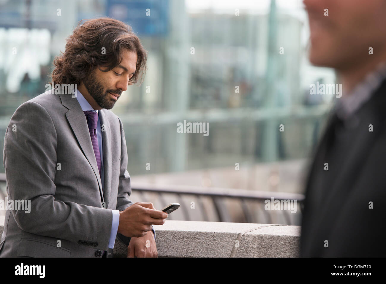 Two men in business suits, on a terrace with a railing. One checking his phone. - Stock Image