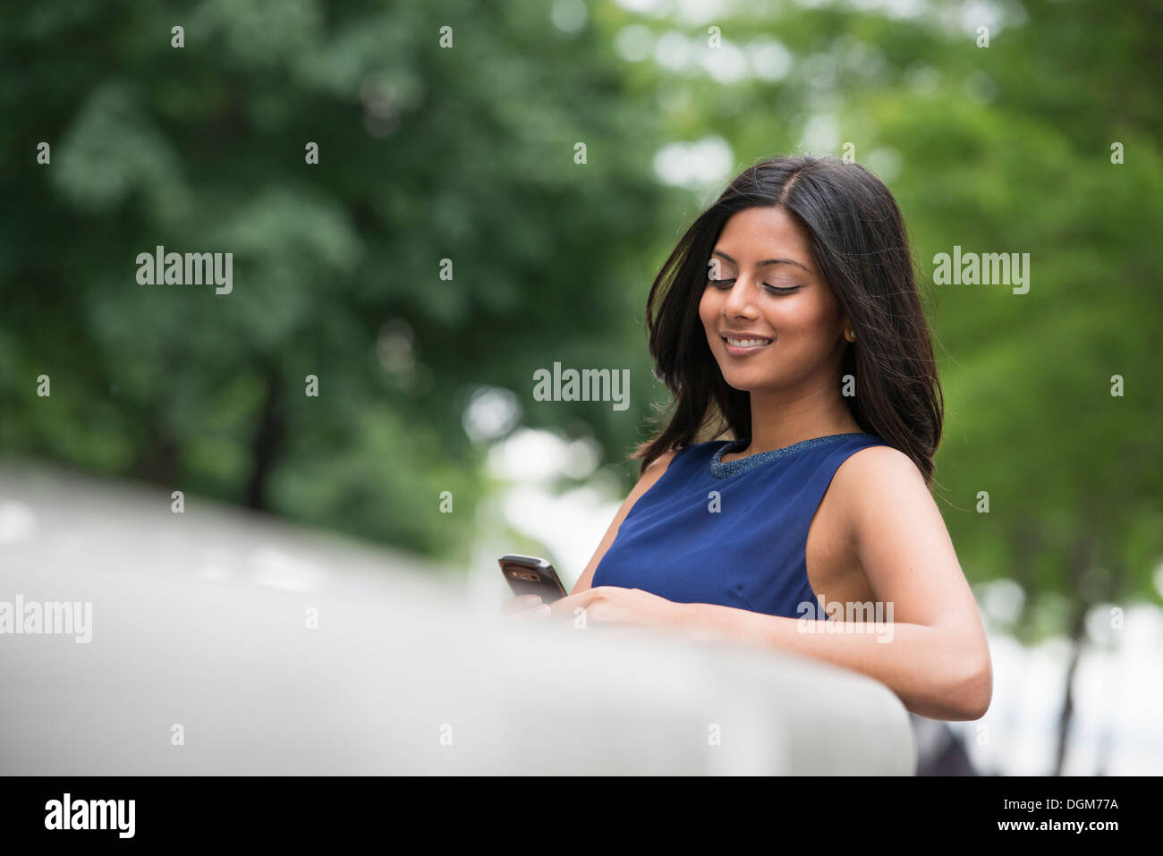 Business people. A woman with long black hair wearing a blue dress. - Stock Image