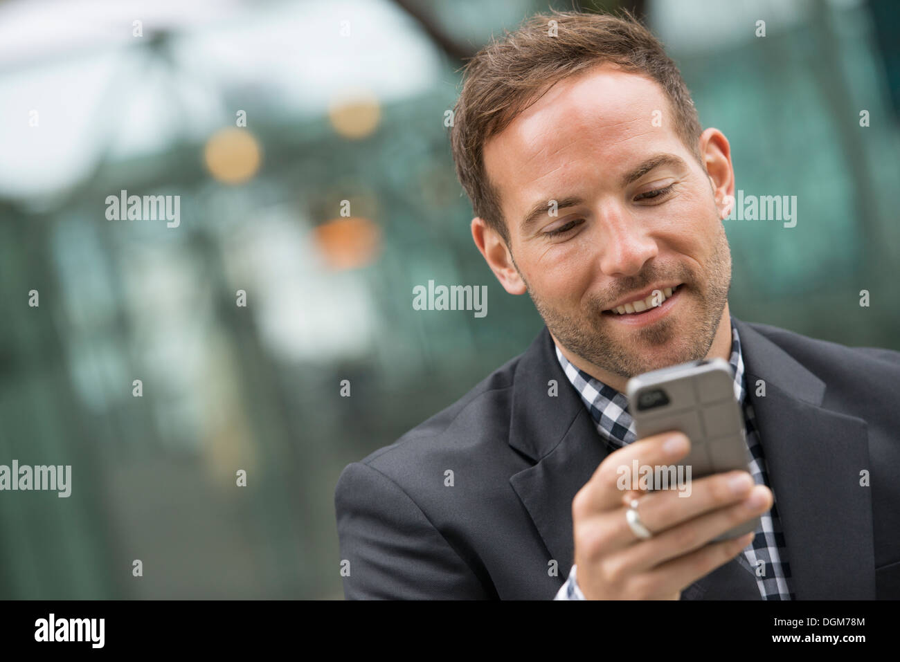 Business people. A man in a business suit. A man with short red hair and a beard, wearing a suit, on his phone. - Stock Image