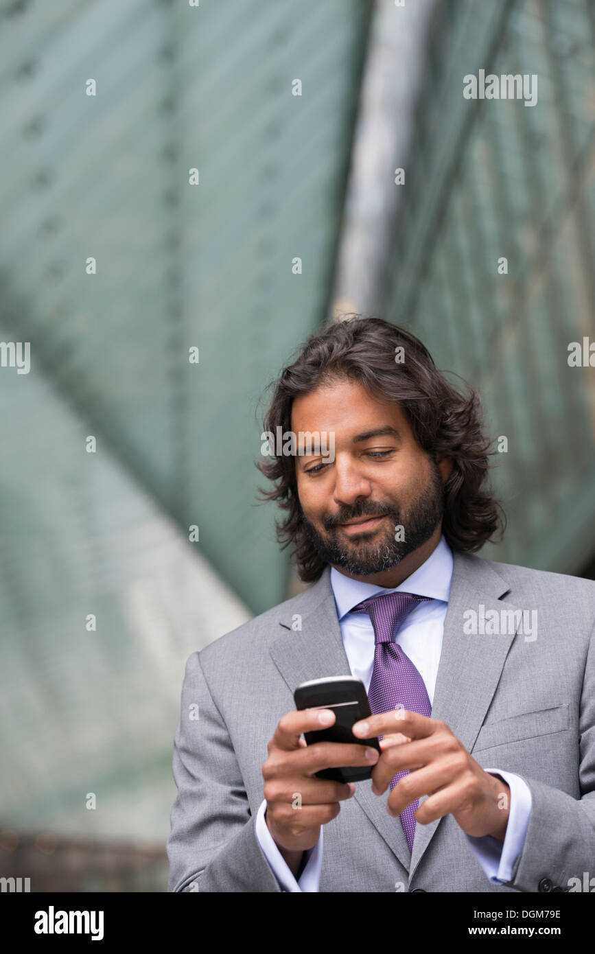 Business people. A man in a business suit with a full beard and curly hair. Using his phone. - Stock Image
