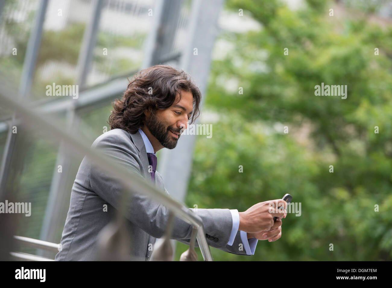 Business people. A man in a suit with brown curly hair and a beard. On his phone. Stock Photo