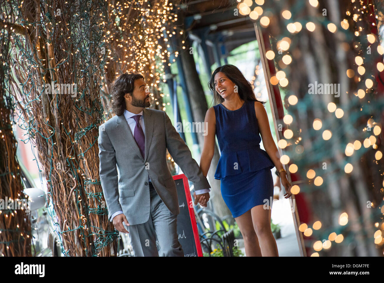 Business people. Two people, a man and woman holding hands and walking under a pergola, lit with fairy lights. - Stock Image