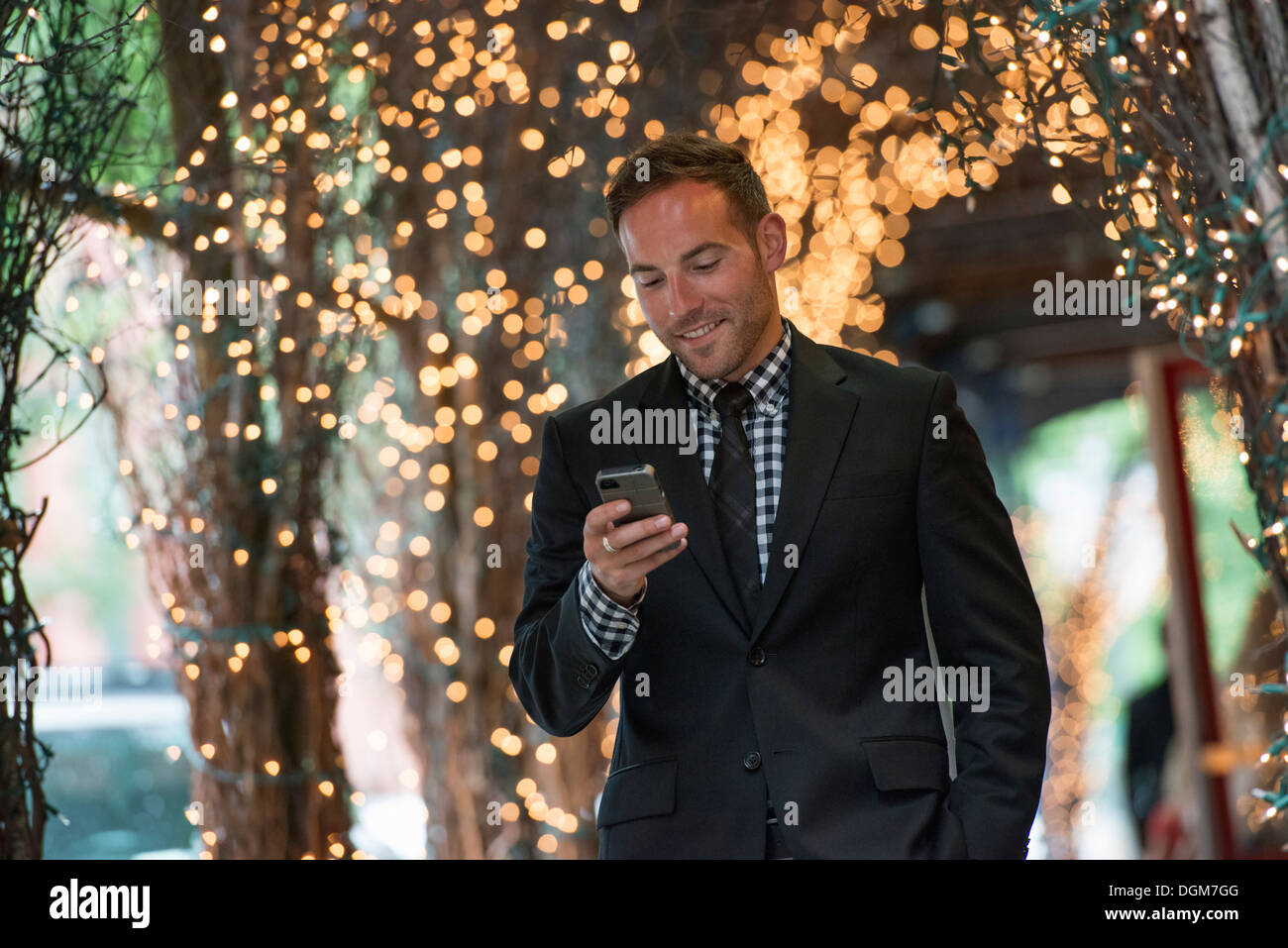 Business people. A man checking his phone, walking under a pergola lit with fairy lights. - Stock Image