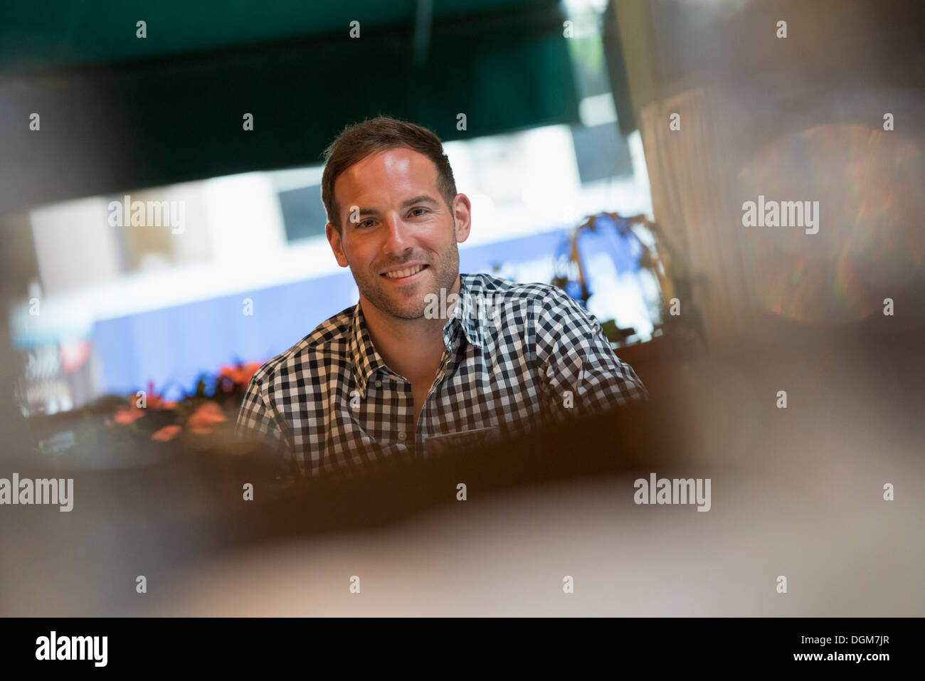 Business people. A man seated at a table in a bar or cafe. - Stock Image